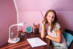 青少年在屋子里在桌上 免版税库存图片