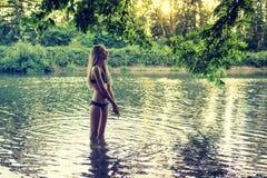 青少年在浅河佩带的比基尼泳装的女孩身分 库存照片