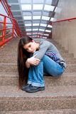 青少年女孩哀伤的学校的台阶 免版税库存照片