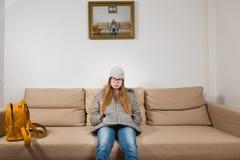 青少年女孩坐沙发早晨在去前教育-早晨是困难的 免版税库存照片