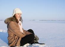 青少年女孩坐的雪 库存照片