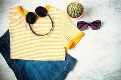 青少年或妇女衣裳和辅助部件成套装备在大理石背景 牛仔布裙子,有黄色条纹的T恤杉和 免版税图库摄影
