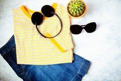 青少年或妇女衣裳和辅助部件成套装备在大理石背景 牛仔布裙子,有黄色条纹的T恤杉和 免版税库存照片