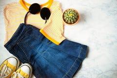 青少年或妇女衣裳和辅助部件成套装备在大理石背景 牛仔布裙子,有黄色条纹的T恤杉,黄色 免版税库存照片