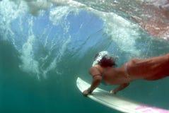 青少年比基尼泳装duckdiving的冲浪者 图库摄影