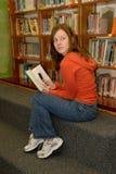青少年电池女孩隐藏的图书馆的电话 免版税库存照片