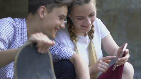 青少年的在智能手机,对社会网络的瘾的夫妇观看的照片 影视素材