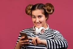 青少年的女孩以听的滑稽的发型用途电话在桃红色背景的音乐 免版税库存图片