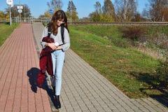 青少年的女孩佩带的玻璃和牛仔裤走的街道 免版税库存照片