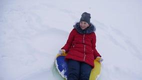 青少年的女孩充当一个冬天公园圣诞节假日 女孩幻灯片在雪的冬天从在雪撬的高小山和  股票视频