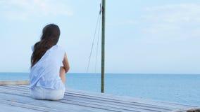 青少年的女孩单独坐一个木桥在海和看起来哀伤在海 股票录像