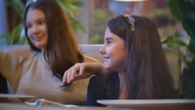 青少年的女孩在咖啡馆沟通是朋友 坐在咖啡馆快餐慢动作录影的儿童十几岁户内 股票录像