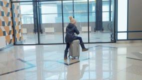 青少年的女孩在手提箱乘坐在等待她的飞行的机场终端在自动扶梯附近 股票录像