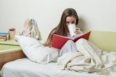 青少年的女孩在睡衣的10岁读书并且拿着茶 免版税库存照片