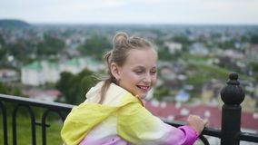 青少年的女孩在观察台的篱芭附近跳在俯视城市的公园 股票录像