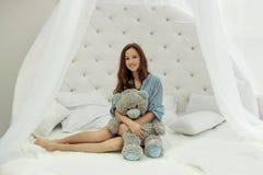 青少年的女孩坐在卧室和拥抱玩具熊的白色圆的床 免版税库存图片