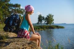 青少年的女孩坐看对海的沙子峭壁 旅行和旅游业概念 库存图片