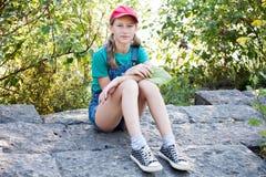 青少年的女孩坐石路面 免版税库存照片