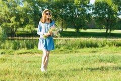 青少年的女孩室外夏天画象有野花花束的,草帽 自然背景,农村风景,绿色草甸, cou 免版税库存照片