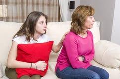 青少年的女孩是哀伤的,因为她的母亲恼怒,当在家时坐沙发 免版税库存照片