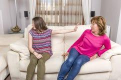 青少年的女孩显示中止姿态给恼怒的母亲,当在家时坐沙发 免版税图库摄影