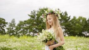青少年的女孩有接近的眼睛的和有在头的在花草甸的花圈和花束的 股票录像