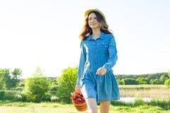 青少年的女孩用篮子草莓,草帽室外夏天画象  自然背景,农村风景,绿色草甸, countr 免版税库存图片