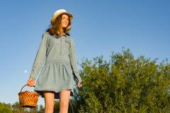 青少年的女孩用篮子草莓,草帽室外夏天画象  自然背景,农村风景,绿色草甸, countr 图库摄影