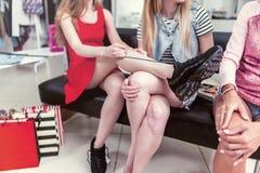 青少年的女孩的播种的图象坐放松在购物的长凳在服装店以后 栓新的年轻时髦的妇女 库存图片
