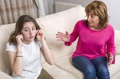 青少年的女孩盖她的耳朵打手势给恼怒的母亲,当在家时坐沙发 库存图片
