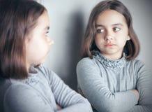 青少年的女孩看她的在镜子的反射 免版税库存照片