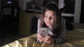 青少年的女孩网络购物在她的智能手机在床上夜间看 小青少年的敞篷女孩写一则消息 股票视频