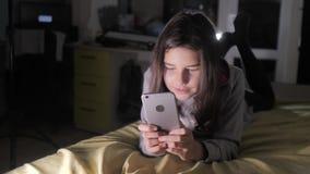 青少年的女孩网络购物在她的智能手机在床上夜间看 小青少年的敞篷女孩写一则消息 影视素材