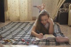 青少年的女孩谁在地板上时在家花费画的时间,当说谎 图库摄影
