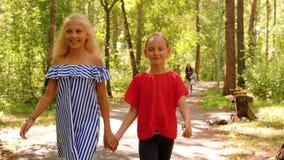 青少年的女朋友在公园举行手上走看照相机和微笑正面图 影视素材