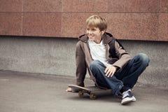 青少年的学校坐滑板在学校附近 免版税库存图片