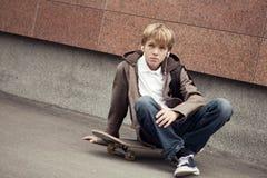 青少年的学校坐滑板在学校附近 免版税图库摄影