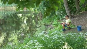 青少年的孩子捉住在池塘的一根钓鱼竿 股票视频