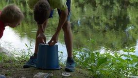 青少年的孩子捉住在池塘的一根钓鱼竿 股票录像