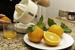 青少年的手的细节拿着有橙色一半和新近地被紧压的柑橘的一台柑橘榨汁器 免版税库存照片