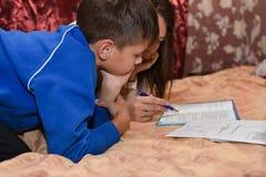 青少年的男孩在做与母亲的晚上学校家庭作业在床上的屋子里 库存照片