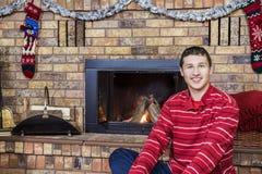 青少年的男孩微笑的坐在舒适壁炉前面装饰了fo 免版税库存图片