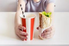 青少年的男孩藏品shawarma三明治卷和甜泡沫腾涌的饮料 免版税库存图片