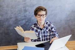 青少年的男孩阅读书和使用膝上型计算机在屋子里 库存照片