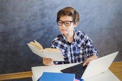 青少年的男孩阅读书和用途膝上型计算机在家 免版税库存照片
