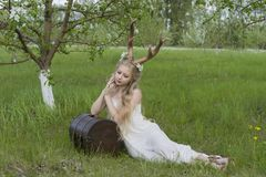 青少年的美丽的白肤金发的有鹿垫铁的o女孩佩带的白色礼服 库存照片