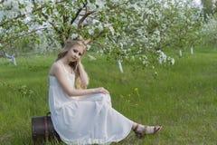 青少年的美丽的白肤金发的有鹿垫铁的o女孩佩带的白色礼服 免版税库存图片