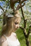 青少年的美丽的白肤金发的有鹿垫铁的o女孩佩带的白色礼服 库存图片