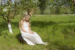青少年的美丽的白肤金发的有鹿垫铁的o女孩佩带的白色礼服 图库摄影