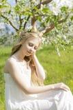 青少年的美丽的白肤金发的有鹿垫铁的o女孩佩带的白色礼服 免版税图库摄影